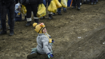 Un niño llora mientras espera junto a otros migrantes y refugiados para efectuar el control de seguridad, una vez cruzada la frontera de Macedonia cerca de la localidad serbia de Miratovac el 26 de enero de 2016. AFP / Armend Nimani