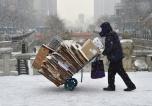 Un hombre empuja un carro con cartones durante una nevada en Seúl, el 16 de febrero de 2016. El banco central de Corea del Sur mantiene sus intereses en un porcentaje récord de 1,5% AFP / Jung Yeon-Je