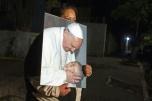 Una mujer con una foto del papa Francisco espera la llegada del sumo pontífice en los exteriores de la nunciatura de Ciudad de México el 16 de febrero de 2016 AFP / Antonio Nava